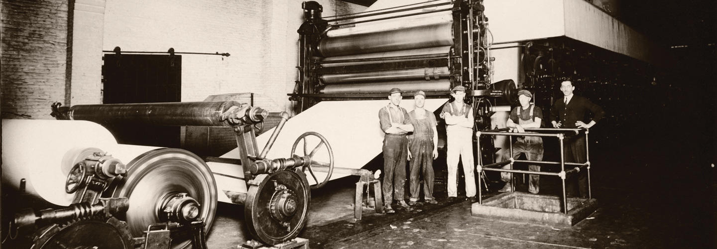 An old black and white photography of a paper machine