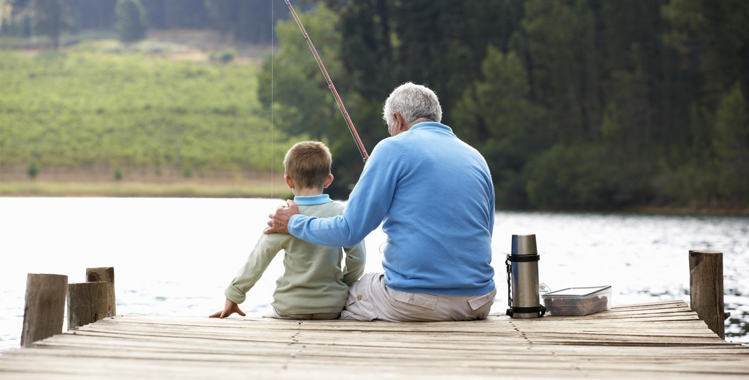 A grandfather with his grandson sitting on a dock and fishing