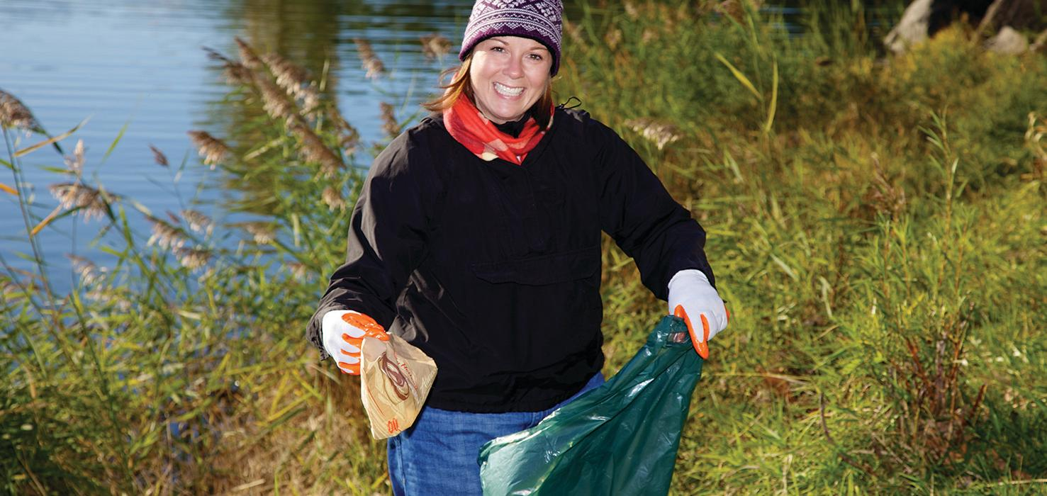 A woman proudly shows the garbage she picked up by a river.