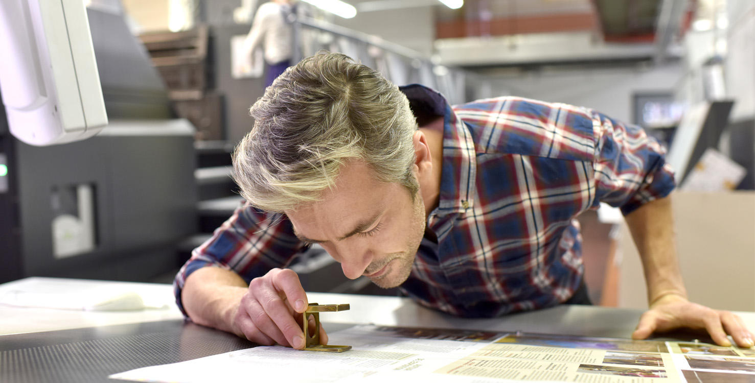 A man examining printed paper with a magnifying glass