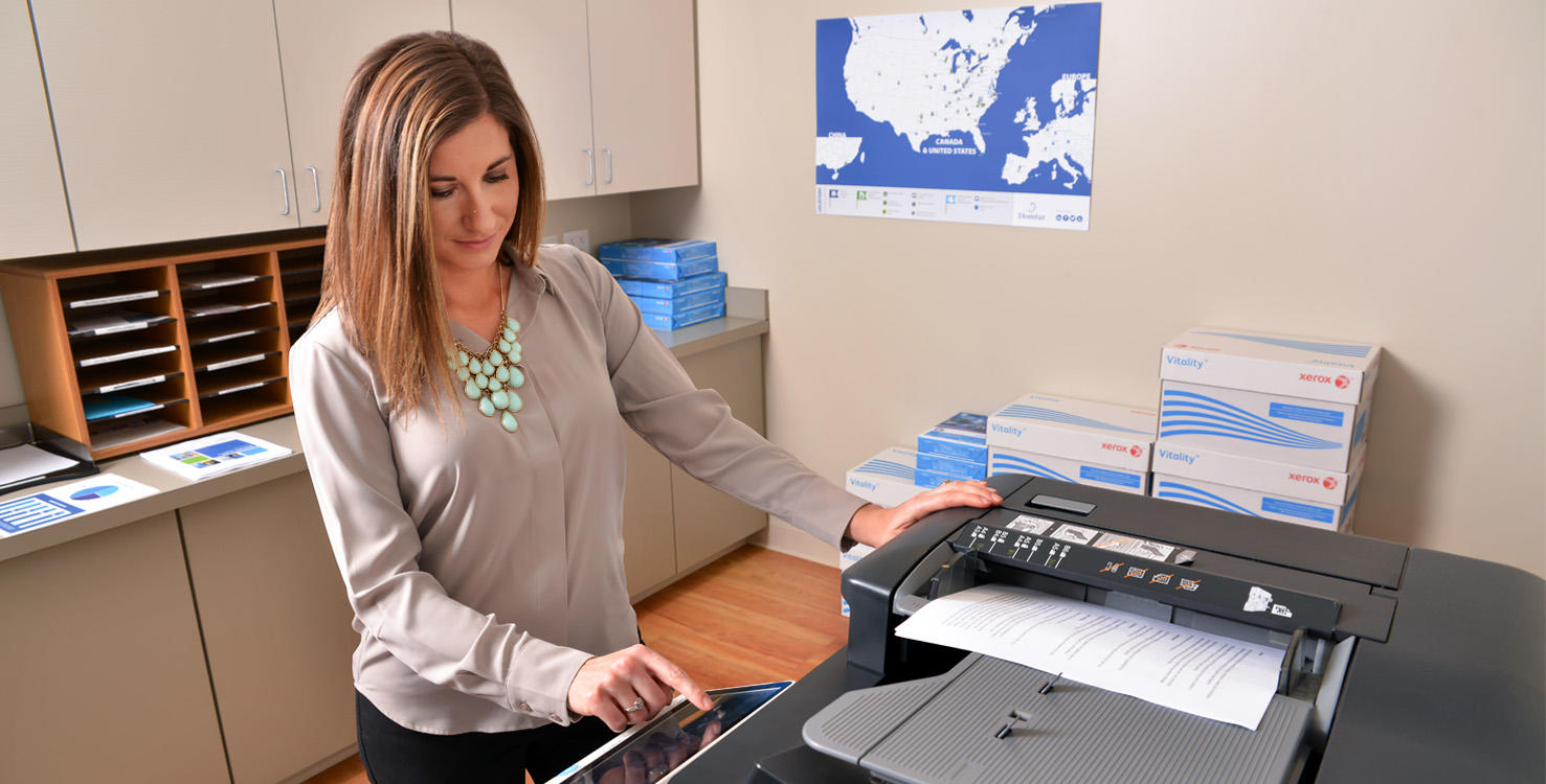 A young woman in an office making copies on Domtar paper