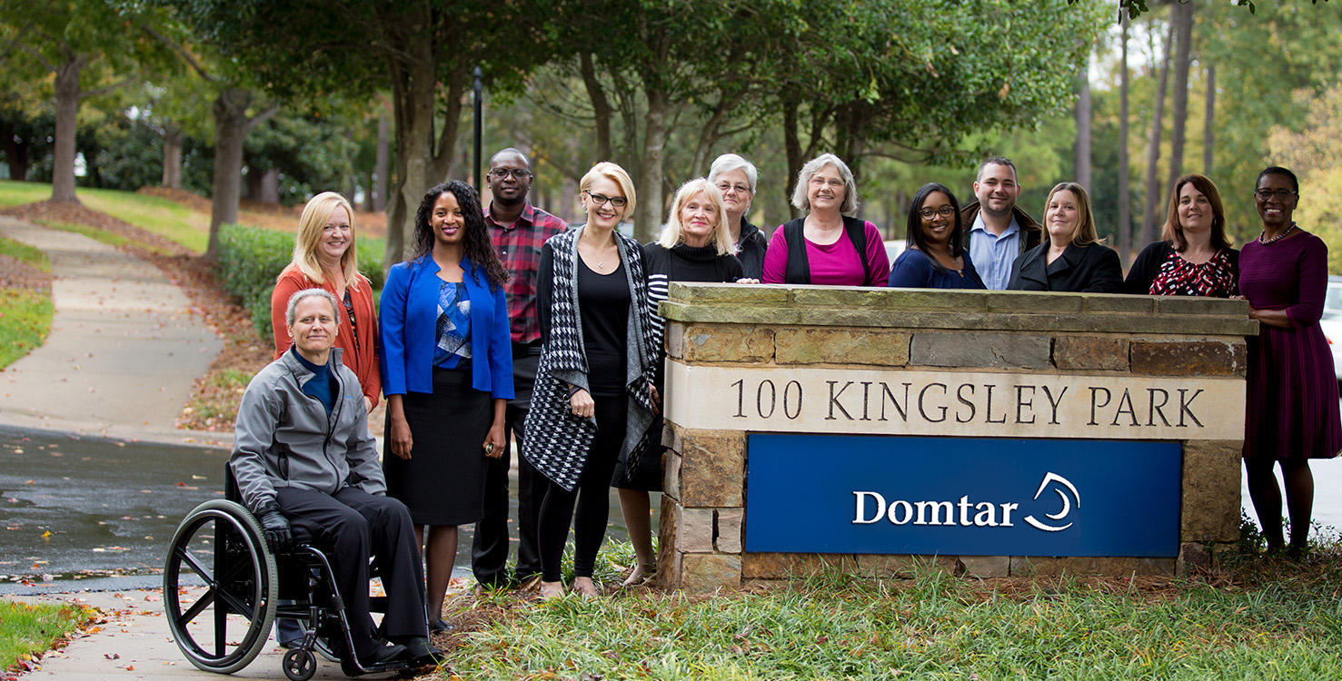 A group of Domtar employees gathered in front of the sign of their building, one of them is in a wheelchair.
