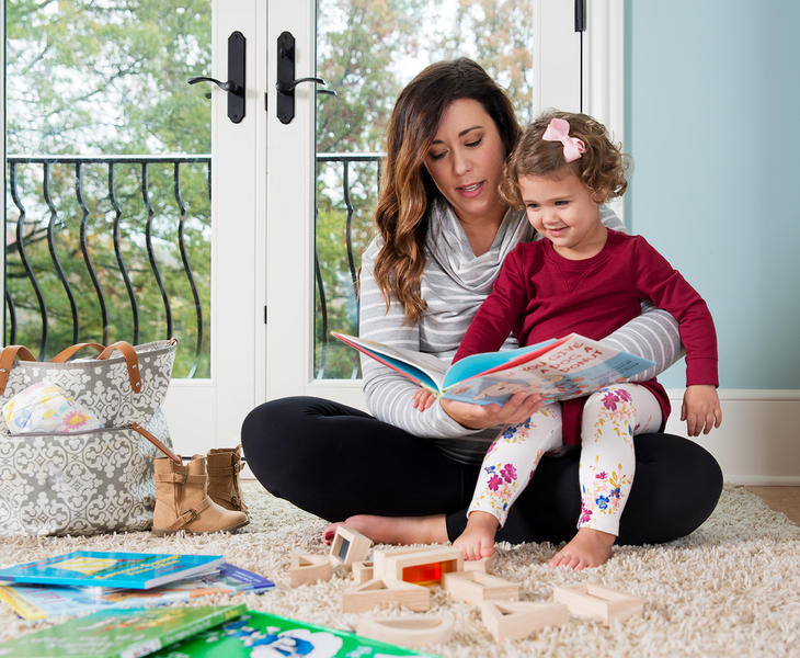 A young mom and her daughter reading a book