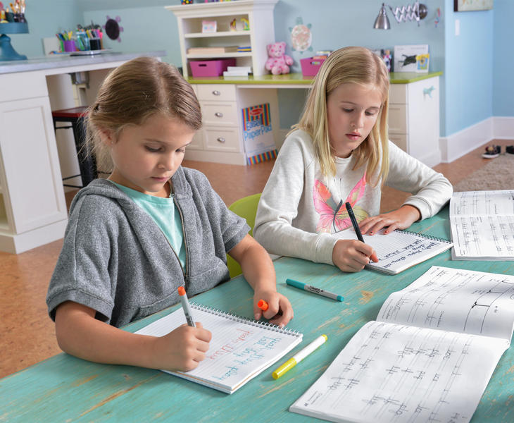 Children writing at home desk